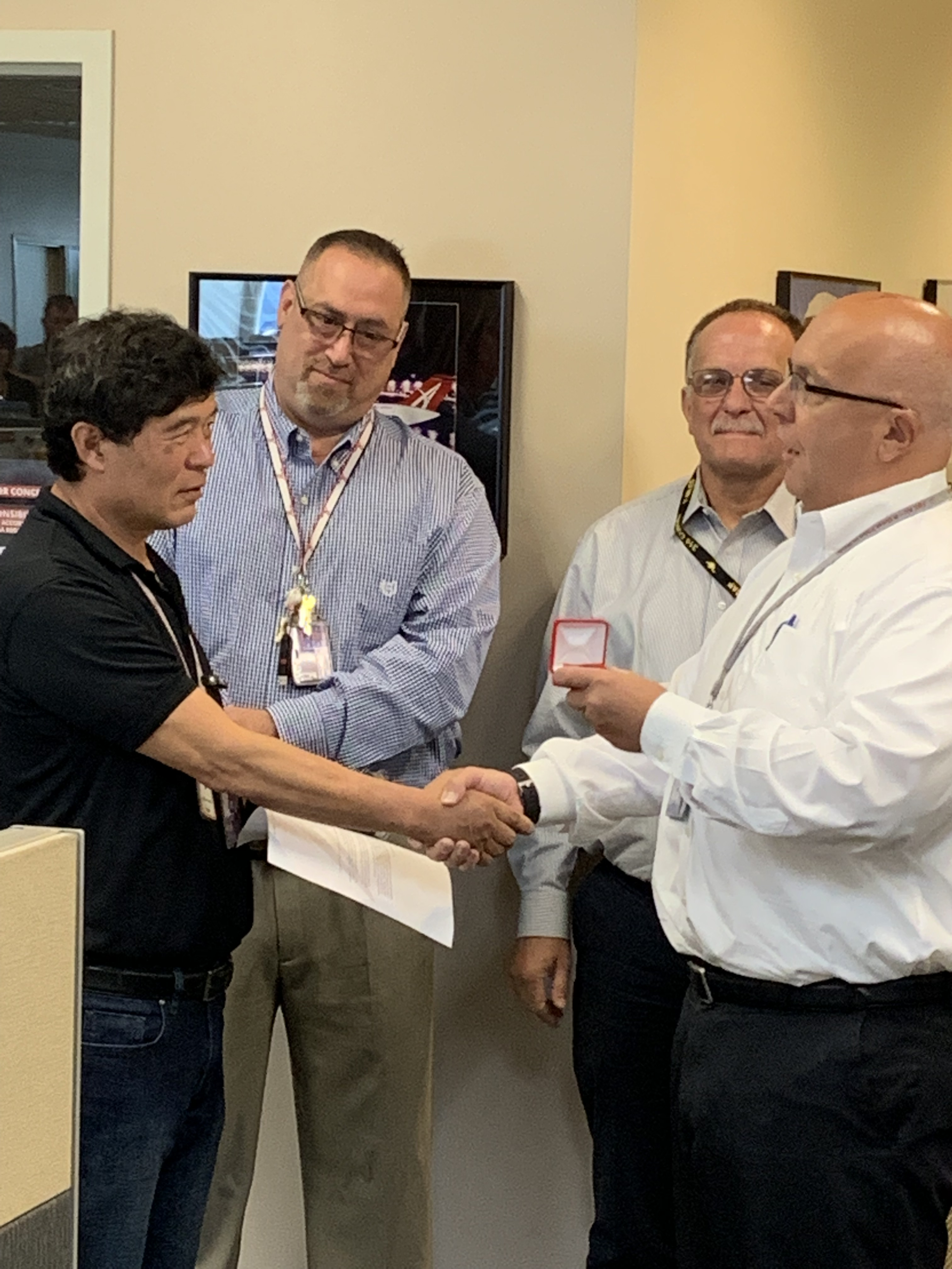 VP Aircraft Maintenance Phil Flowers congratulates Jong Park. In the back are Manager of Line Maintenance (CVG) Mark Stevens and Director of Line Maintenance Brad Hamlin.